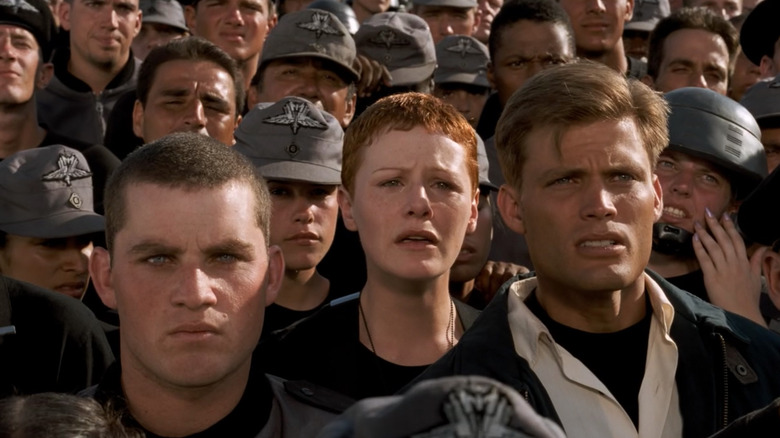Starship trooper soldiers watch the news