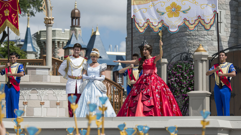 Cinderella, Prince Charming, and Elena of Avalor on the stage in front of Cinderella's Castle in Walt Disney World